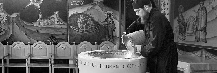 An Orthodox priest prepares the Holy Font for a christening at St Andrew's Greek church in Kentish Town