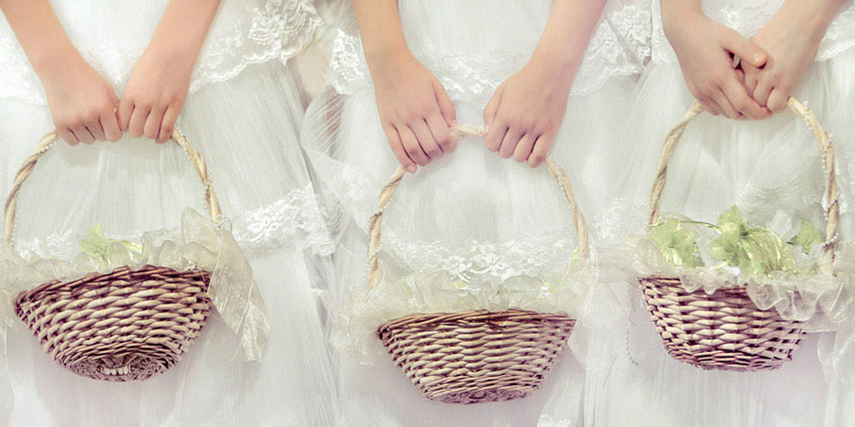 Three flower girls holding traditional baskets