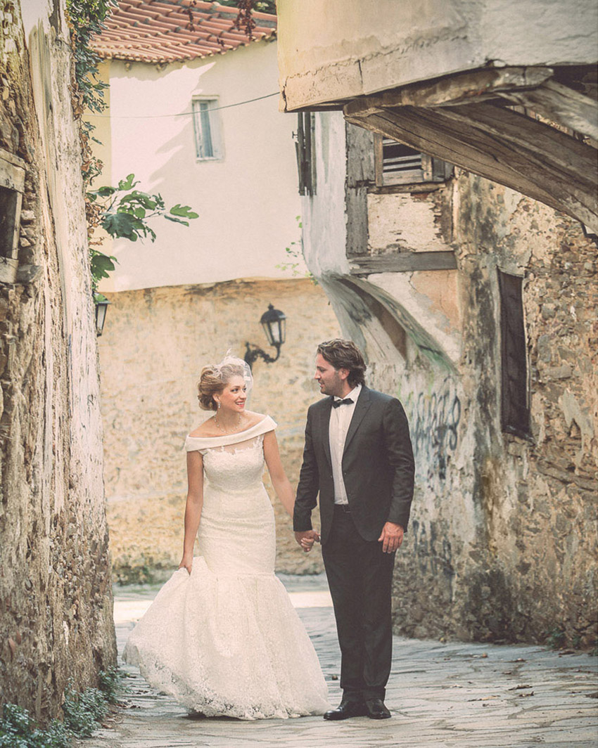 A just-married couple walking in an old Greek village