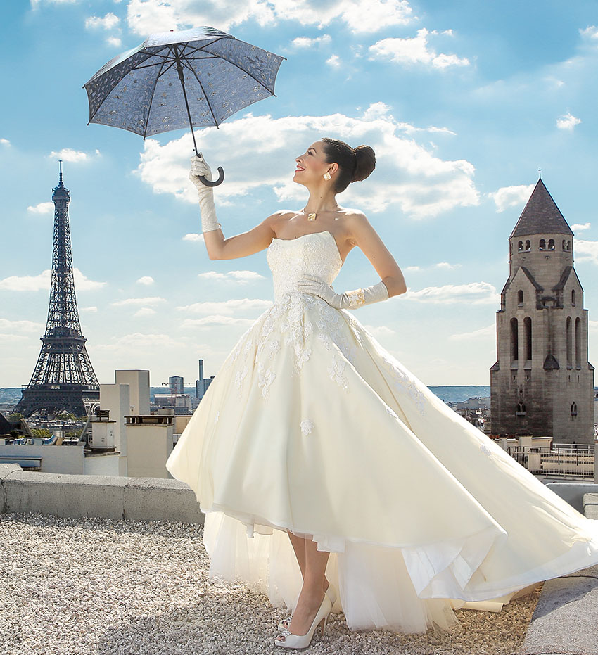 Bride holding a wedding umbrella posing having Eiffel Tower as a backdrop